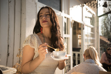 young lady holding cup of tea while siting outdoors