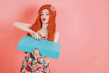 Redhead girl open a gift box for the holiday. Woman with long red hair in trendy summer dress with blue present box on pink background. Present gift on Birthday holiday.