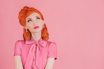 Woman with great idea in pink retro dress. Minimal color concept. Redhead model with retro hairstyle on pastel pink background. Pastel color. Lady elegance. Magnificent concept idea. Minimal style
