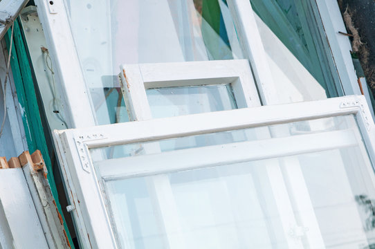 Many different construction debris from old wooden window frames  together with glass and white paint piled. Concept of replacement of old wooden window frames with new ones.