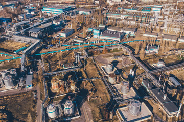 Aerial view of industrial factory or plant buildings with steel storage construction tanks and pipes
