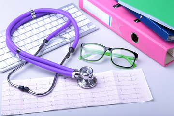 Medical record concept with stethoscope over pile of folders. Keyboard, glasses, pen, RX prescription. Selective focus