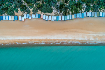 Bathing boxes, sandy beach, and turquoise ocean water - aerial top view