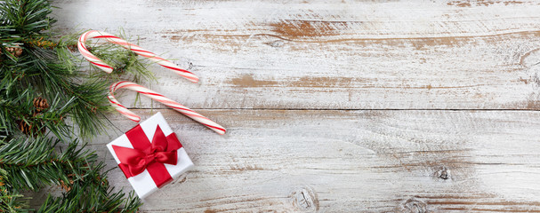 Christmas gift box with border of fir branches and candy canes on white rustic wooden background
