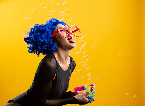 Woman with colorful blue hair blowing and popping bubbles