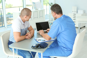 Male medical assistant consulting patient in clinic