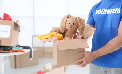 Male volunteer holding box with donations indoors. Space for text