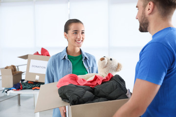 Young woman giving box with donations to male volunteer indoors