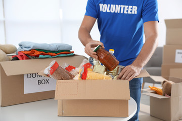 Male volunteer collecting donations at table indoors