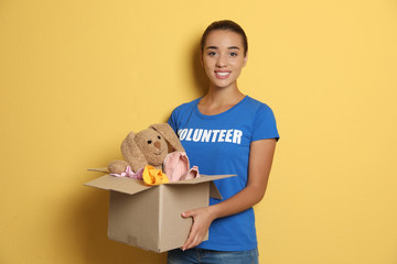Female volunteer holding box with donations on color background