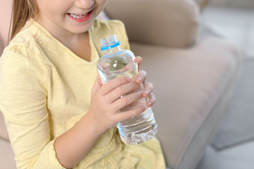 Cute little girl holding bottle with water indoors