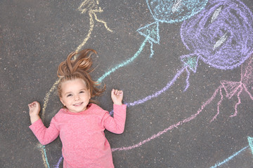 Little child lying near chalk drawing of balloons on asphalt, top view