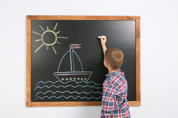 Little child drawing ship with colorful chalk on blackboard