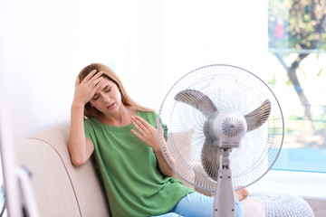 Woman suffering from heat in front of fan at home