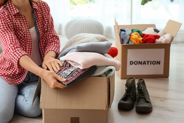 Woman packing clothes into donation box at home