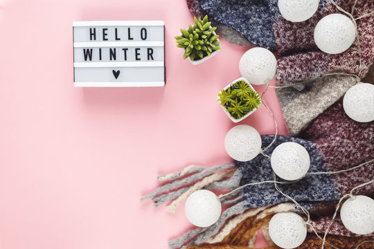 Christmas concept flat lay. Warm, cozy winter clothing, light box  and Christmas decorations frame on white background