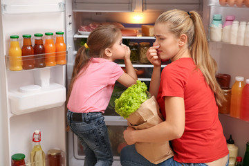 Young mother and daughter holding noses cause of bad smell from refrigerator at home