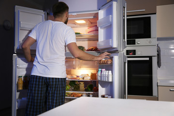 Young man looking for food in refrigerator at night