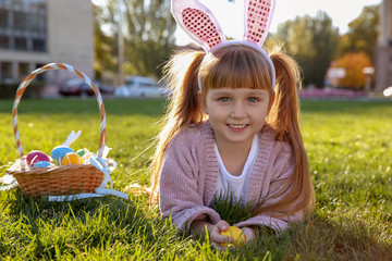 Cute little girl with bunny ears and basket of Easter eggs in park