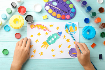 Girl painting picture of spaceship on table, top view