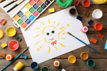 Flat lay composition with child's painting of smiling sun on table