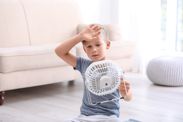 Little boy suffering from heat in front of fan at home