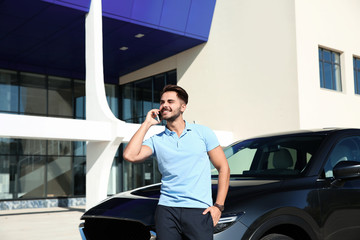 Young man talking on phone near modern car, outdoors