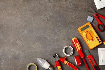 Flat lay composition with electrician's tools and space for text on gray background