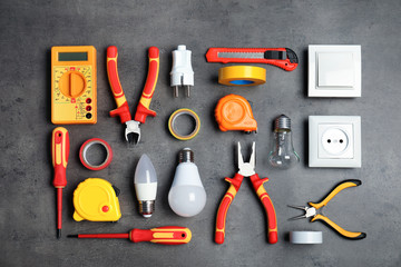 Flat lay composition with electrician's tools on gray background