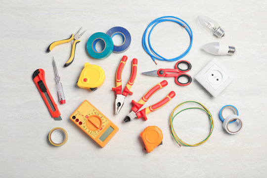 Flat lay composition with electrician's tools on light background