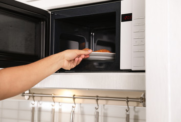 Young man putting plate with croissants in microwave oven, closeup