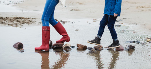 People walking on stones at the beach