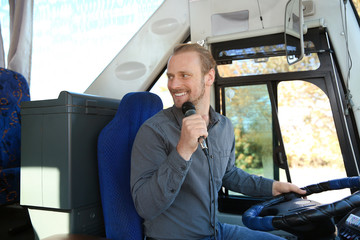 Professional driver making announcement for passengers in bus