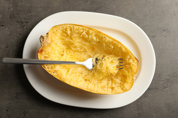 Plate with cooked spaghetti squash and fork on gray background