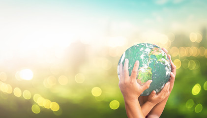 Community care concept: Human hands holding earth global over blurred green city background. Elements of this image furnished by NASA