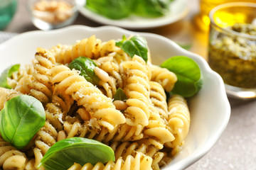 Plate of delicious basil pesto pasta on table, closeup