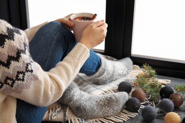 Woman relaxing with hot winter drink near window. Cozy season