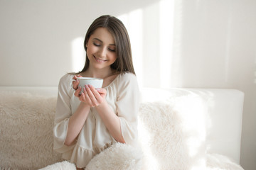 beautiful girl with a cup of coffee on the bed
