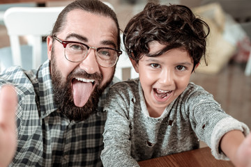 Funny faces. Bearded dark-haired father and cute handsome son making funny faces while making photo together