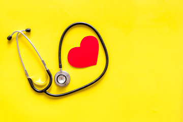 Health care concept. Stethoscope near heart sign on yellow top view space for text