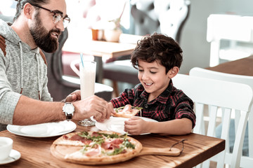 Pizza for lunch. Bearded caring father and cute handsome son having tasty pizza for lunch on weekend
