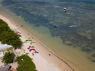 Kiteboarding, kite surf. Extreme sport kitesurfing in tropical blue ocean, clear beach. Aerial views, top view from drone of kitesurfing on the waves of the beautiful sea. Kite surfer rides the waves