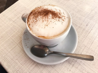 Cup of cappuccino with cinnamon on table