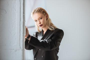 attractive blonde woman posing in black suit on grey