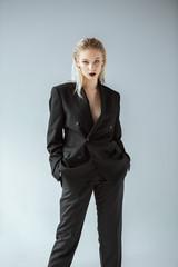 fashionable stylish blonde girl posing in black suit isolated on grey