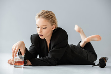 attractive fashionable woman in black trendy suit holding glass of whiskey and lying on grey