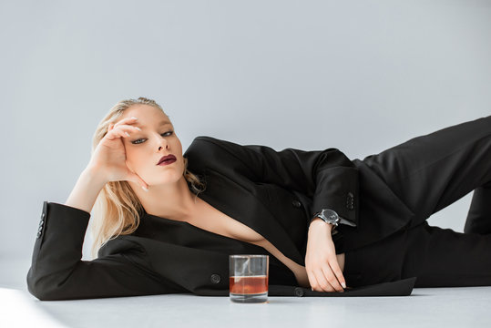 beautiful stylish half naked woman in black trendy suit lying on grey with glass of whiskey
