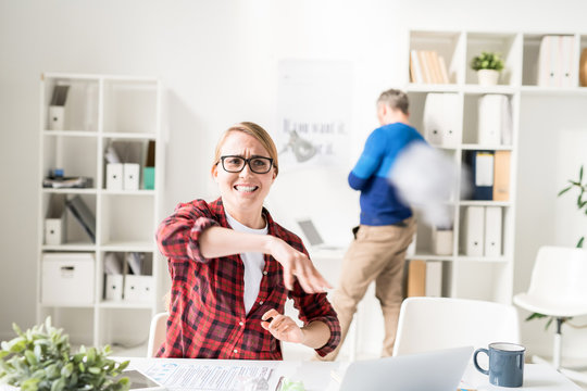 Failure of marketing specialist: frustrated displeased young woman in checkered shirt sitting at desk with papers and laptop and throwing  crushed paper while having problem with project