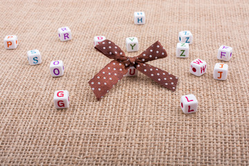 A ribbon and scattered dice-sized alphabet cubes on a textured surface