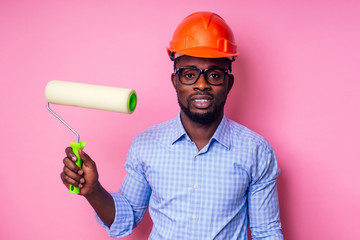 black man African American holding paint roller in hand paints the wall in pink color .happy african builder painting inside the house,businessman wears a helmet hard hat.young guy is painting